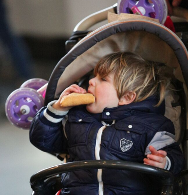 Child eating Panzerotti on a buggy